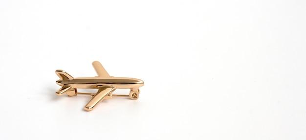 Broche de oro en forma de avión sobre un fondo blanco.