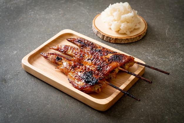 Brocheta de alitas de pollo a la parrilla o barbacoa con arroz glutinoso