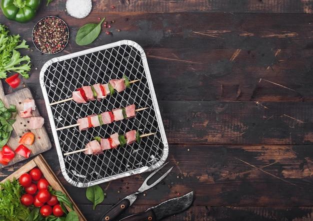 Brocheta de cerdo cruda con pimentón en parrilla de barbacoa de carbón desechables con verduras frescas sobre fondo de madera