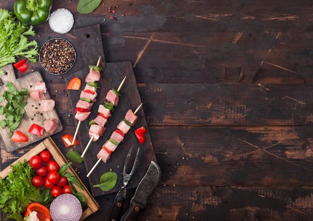 Brocheta de cerdo cruda con pimentón sobre una tabla de cortar con verduras frescas sobre fondo de madera
