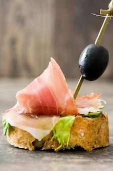 Brocheta de jamón serrano español con aceituna y lechuga en mesa de madera