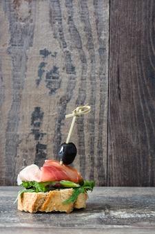 Brocheta de jamón serrano español con aceituna y lechuga