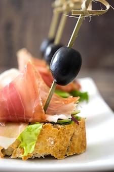 Brocheta de jamón serrano español con aceitunas y lechuga en la mesa de madera de cerca