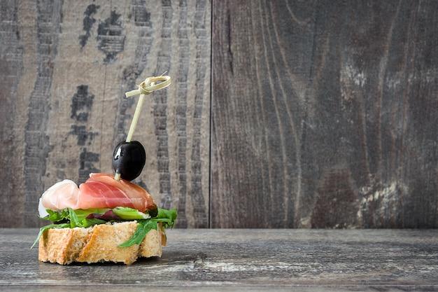 Brocheta de jamón serrano español con aceitunas y lechuga en mesa de madera copia espacio