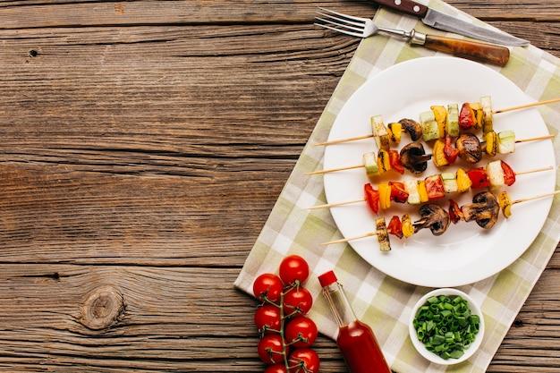 Brocheta de kebab a la parrilla servida en un plato blanco sobre mesas de madera