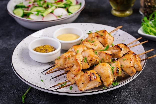Brocheta de pollo a la parrilla y ensalada con pepino, rábano, cebolla