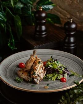 Brocheta de pollo servida con cerezas y ensalada verde