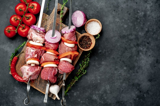 Brochetas de carne cruda. barbacoa de carne con verduras y especias.