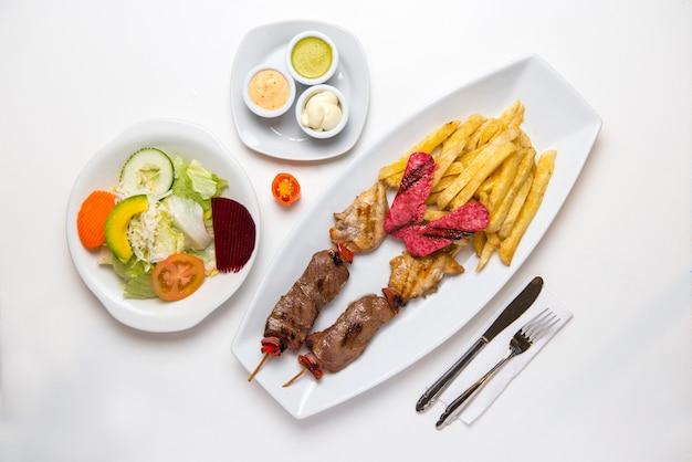 Brochetas de carne y pollo con papas fritas, cerdo, ensalada y cremas