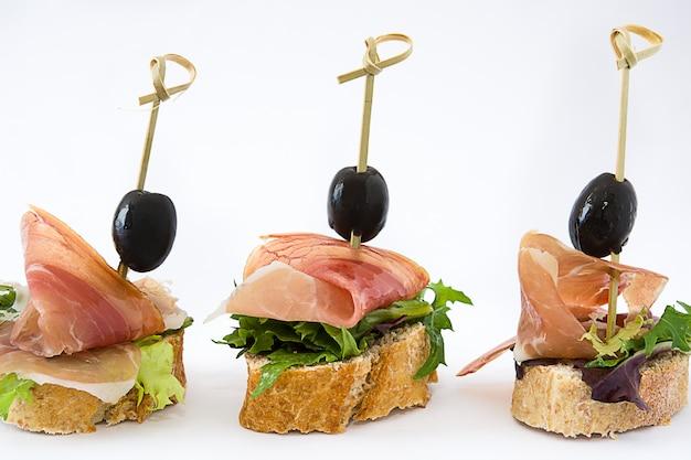 Brochetas finas de jamón serrano español con aceituna y lechuga aislado sobre superficie blanca