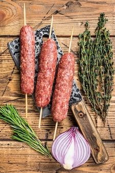Brochetas de kebabs kofta o lula crudas frescas en una cuchilla de carnicero con hierbas. fondo de madera. vista superior.