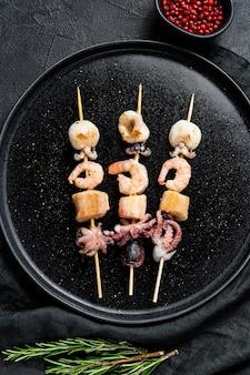 Brochetas de madera con camarones, pulpo, calamares y mejillones kebab con mariscos. vista superior