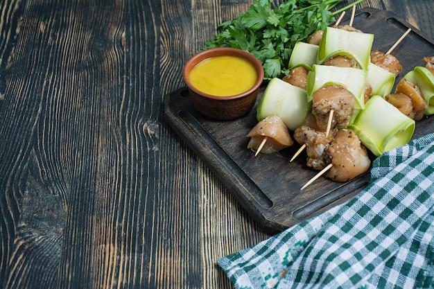 Brochetas en un pincho con calabacín con salsa y verduras en una tabla de cortar