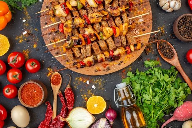 Brochetas de pollo asado a la parrilla en la mitad superior de la tabla de madera y otras cosas en la mesa