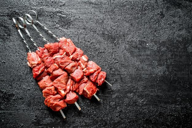 Brochetas de shish kebab crudo sobre mesa de madera negra