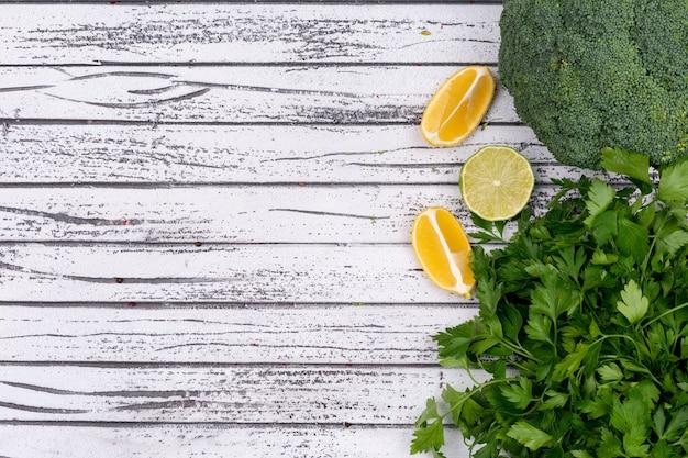 Brócoli amarillo limón y perejil con espacio de copia en superficie de madera
