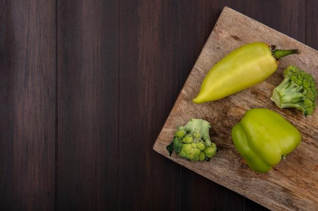 Brócoli de espacio de copia de vista superior con pimientos verdes en tabla de cortar sobre fondo de madera
