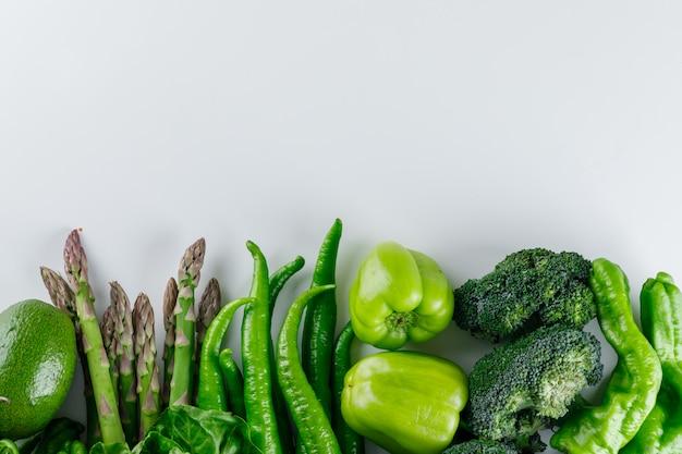 Brócoli con espárragos, pimientos, aguacate y lechuga sobre una mesa blanca