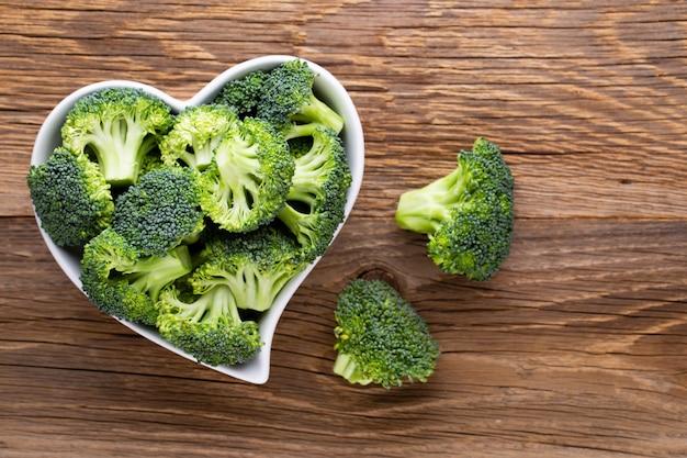 Brócoli fresco en un recipiente en forma de corazón sobre una mesa de madera.