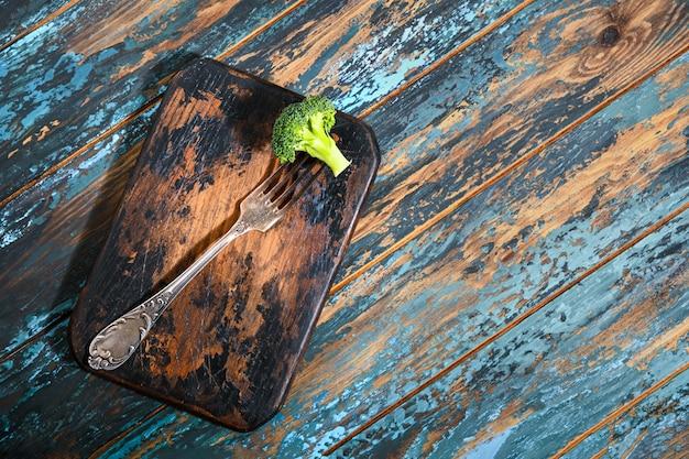 Brócoli en tenedor antiguo sobre tablero de cocina quemado en mesa azul de madera teñida en bruto.