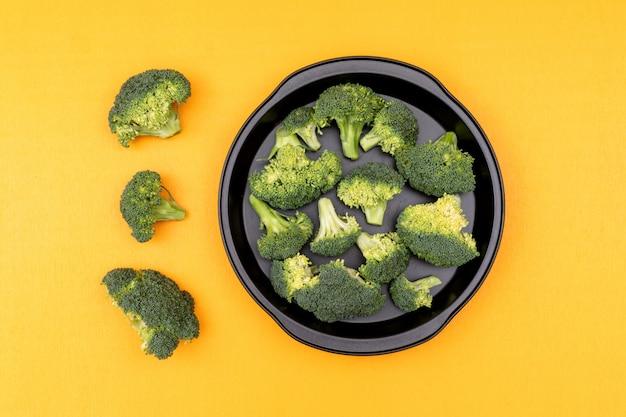 Brócoli verde crudo fresco en una sartén sobre superficie amarilla
