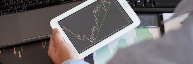 Broker de empresario analizando gráficos de datos financieros e informes en pantalla