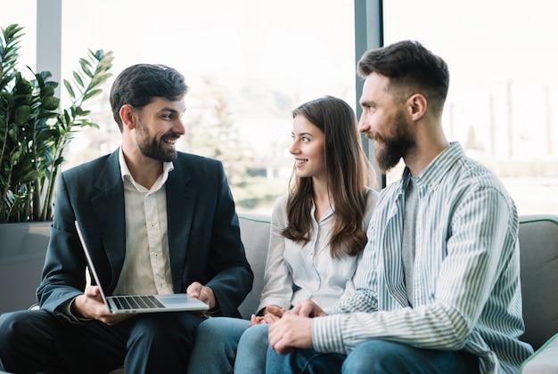Broker de seguros que consulta a clientes en la oficina