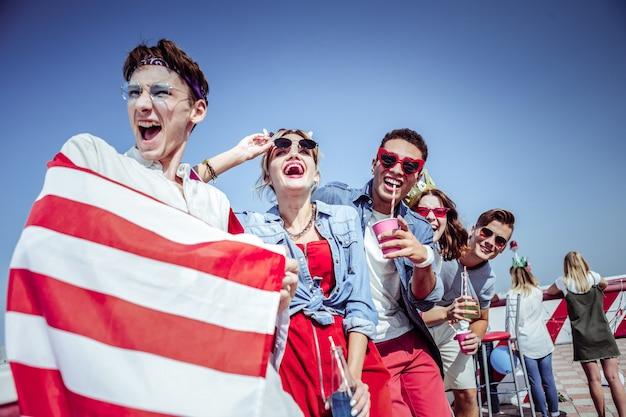 Broma de verdad. chico amable gritando mientras expresa su alegría, demostrando bandera