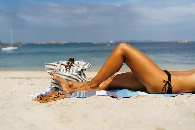 Broncee las piernas de la mujer de las vacaciones de la playa que mienten en la toalla de arena que se relaja en vacaciones de verano.