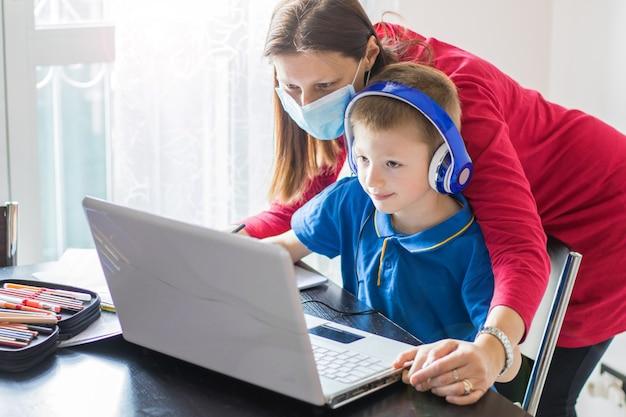 Brote de coronavirus. cierre y cierre de escuelas. madre ayudando a su hijo con mascarilla estudiando clases en línea en casa.