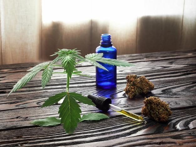 Brotes y aceite de marihuana en una mesa rústica