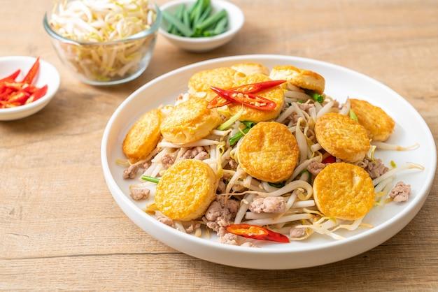 Brotes de soja salteados, huevo tofu y carne de cerdo picada - estilo de comida asiática