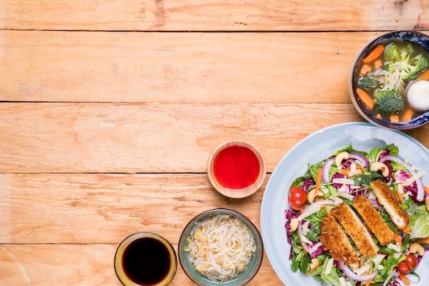 Brotes de soja; sopa; filete; ensalada con salsas en escritorio de madera