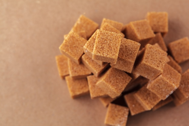 Brown cubitos de azúcar de caña en un marrón claro