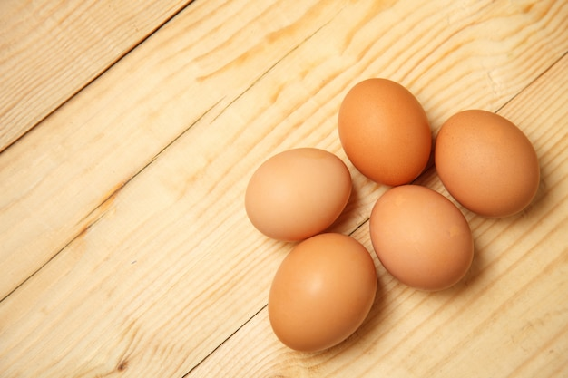 Brown huevos bien iluminados ubicados en grupos sobre fondo de madera