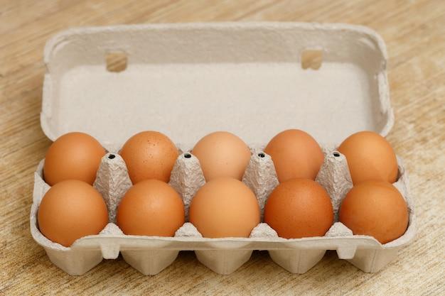 Brown huevos de gallina en caja de cartón en la mesa de madera
