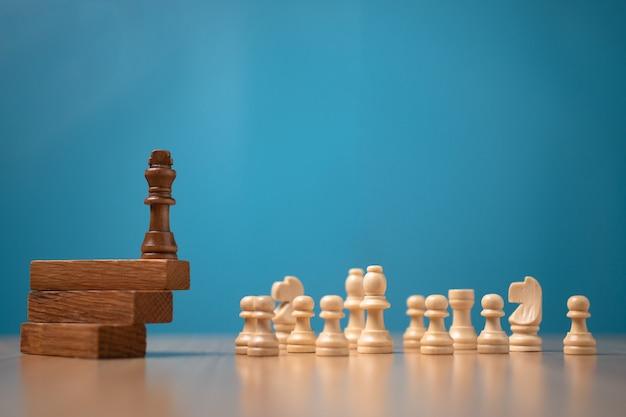 Brown rey ajedrez de pie sobre un soporte de madera. el concepto de líderes en buenas organizaciones debe tener una visión