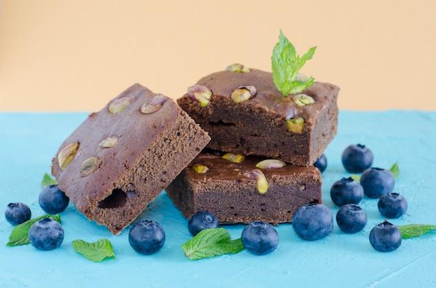 Brownie con arándanos sobre fondo azul.