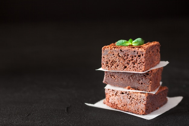 Brownie de chocolate cuadrados piezas en la pila en un plato blanco con nueces