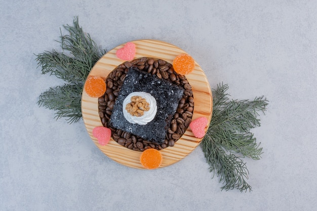 Brownie de chocolate con granos de café sobre placa de madera.