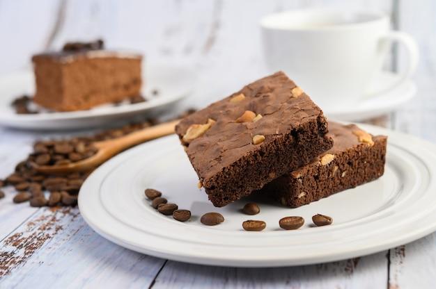 Brownie de chocolate en un plato blanco y granos de café en una cuchara de madera.