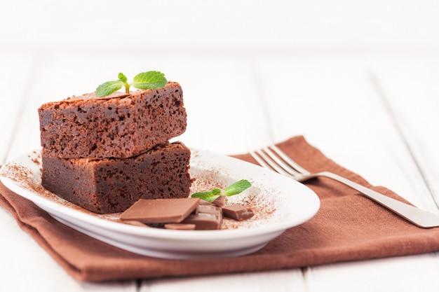 Brownie de chocolate, trozos cuadrados en una placa blanca decorada con hojas de menta y cacao en polvo