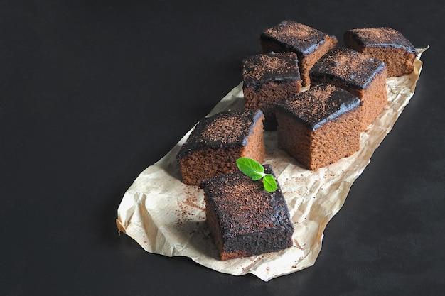 Brownie clásico recién horneado en pergamino se colocan sobre una superficie negra