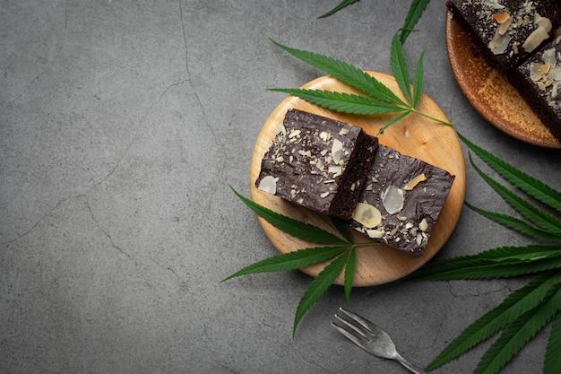 Brownies de cannabis y hojas de cannabis en tabla de cortar de madera