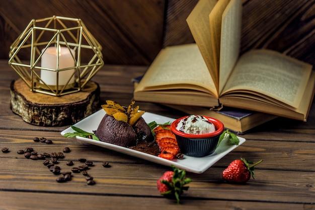 Brownies de choco servidos con salsa cremosa y combinación de frutas