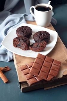 Brownies de chocolate con una barra de chocolate con leche y una taza de café.