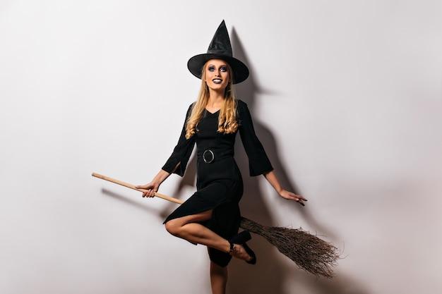 Bruja agradable bien formada sentada en su escoba. adorable maga en sombrero mágico.