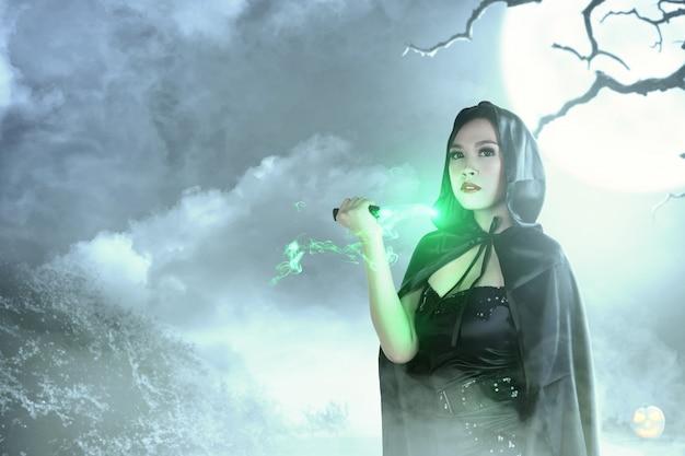 Bruja asiática con capucha negra haciendo magia ritual con un cuchillo