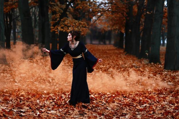 Bruja en el bosque salvaje de otoño