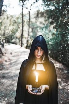 Bruja en capucha con vela en el bosque
